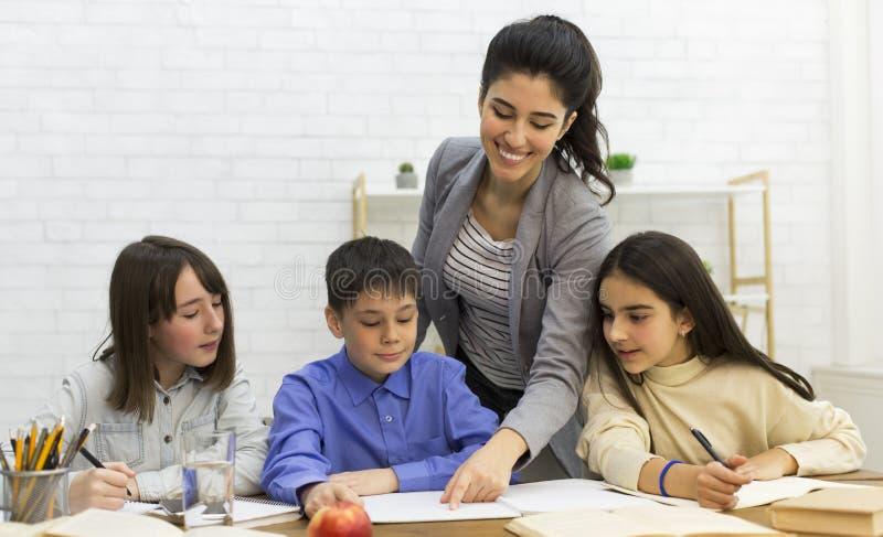 Teacher helping children in classroom, doing homework together stock photo