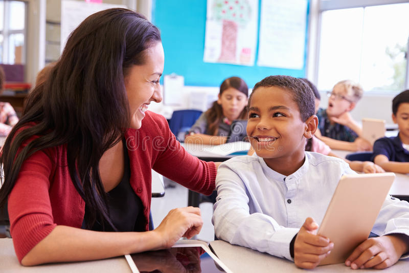 Teacher helping elementary school boy using tablet computer royalty free stock image