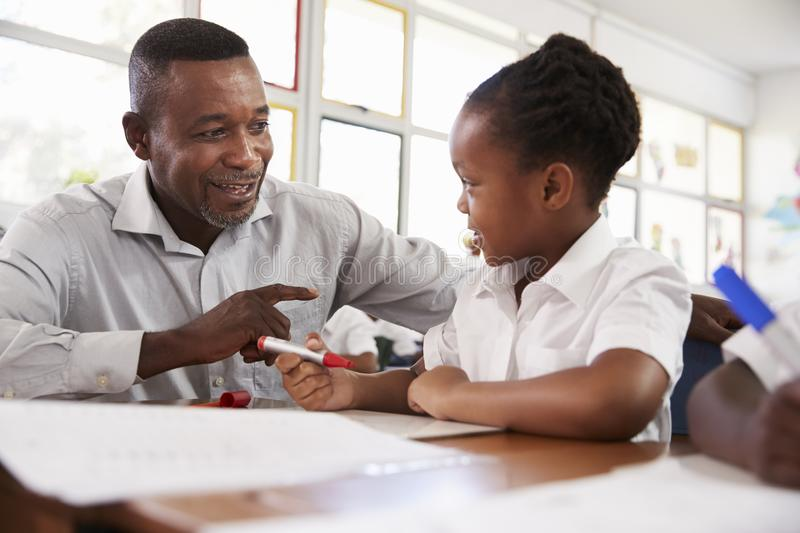 Teacher helping elementary school girl at her desk, close up royalty free stock photo