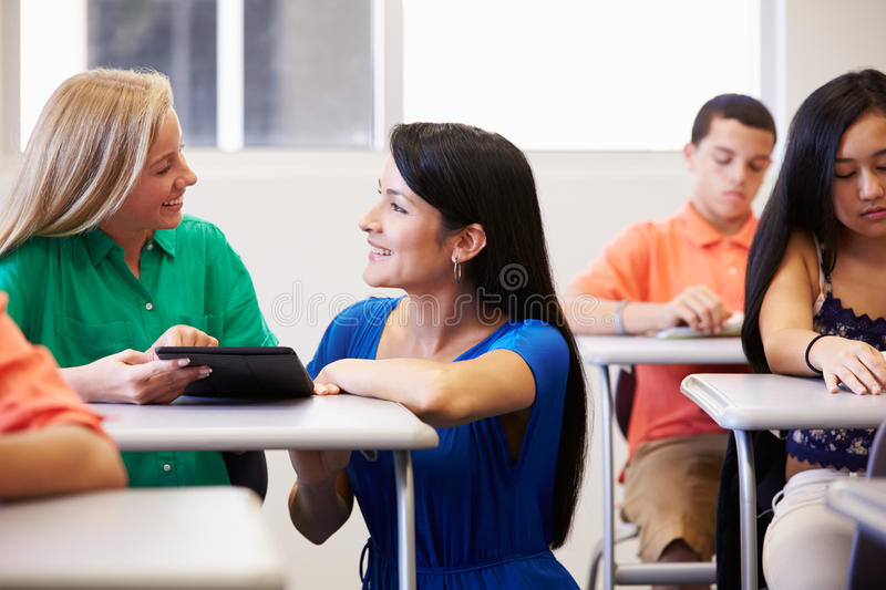 Teacher Helping Female High School Student In Classroom stock photos