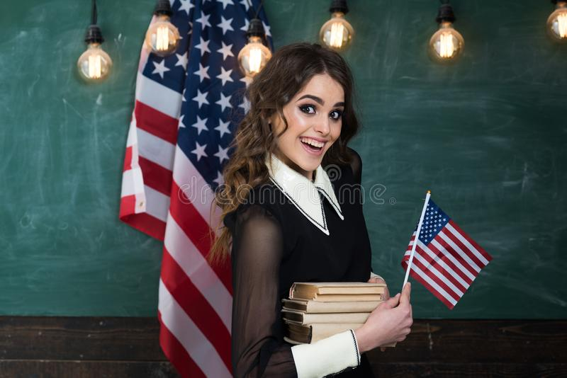 Teacher helping kids with computers in elementary school on the USA national flag background. Teacher conveys sense of stock images