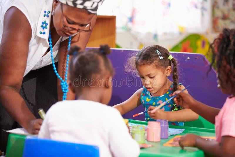 Teacher helping kids in a preschool class, close up stock image