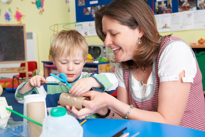 Teacher Helping Little Boy To Build Model In Art Class. Teacher And Boy Build Junk Model In Pre School Class stock photo