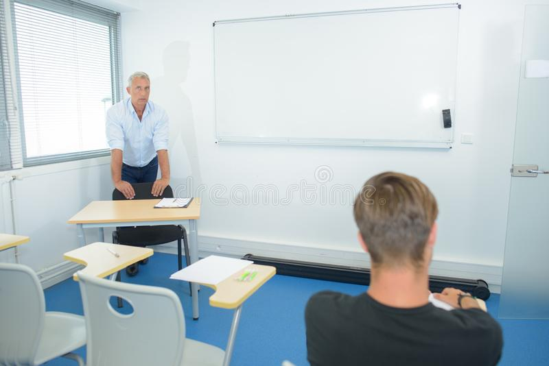 Teacher helping one student after class royalty free stock photos
