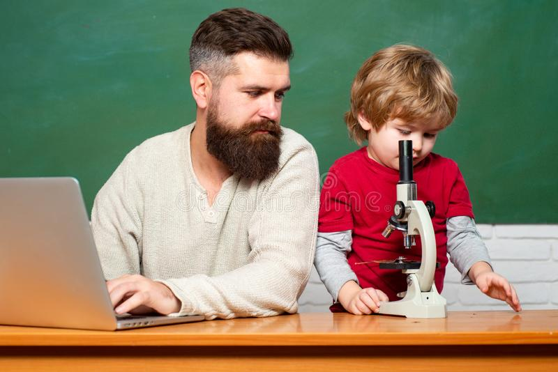 Teacher helping pupils studying on desks in classroom. Young boy doing his school homework with his father. Chalkboard royalty free stock photo