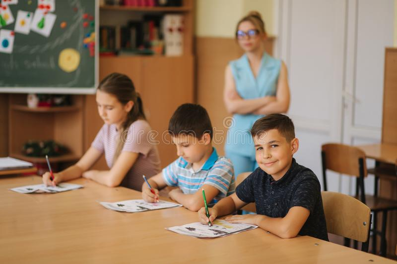 Teacher helping school kids writing test in classroom. education, elementary school, learning and people concept royalty free stock images