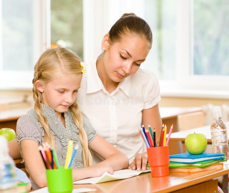 Teacher helping schoolgirl with schoolwork in classroom stock photos