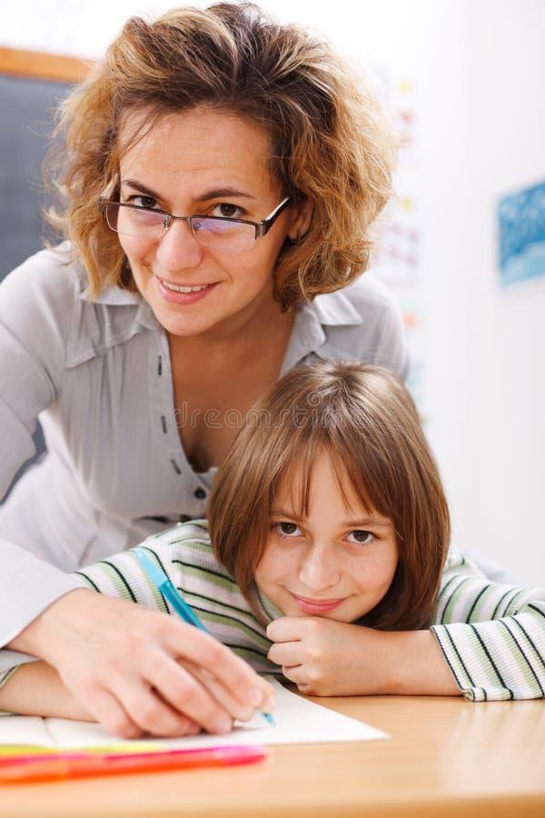 Teacher helping schoolgirl writing