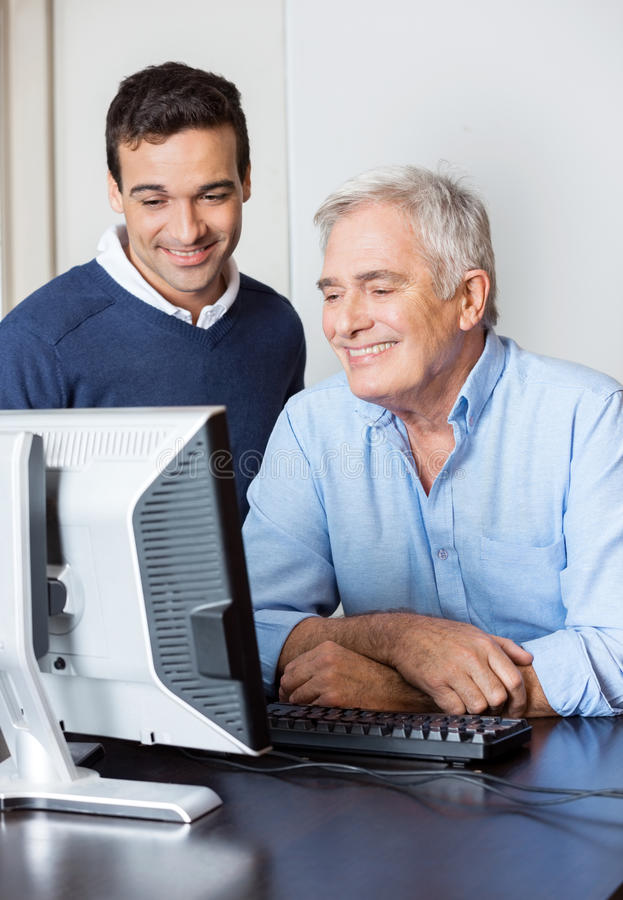 Teacher Helping Senior Student In Computer Lab royalty free stock images