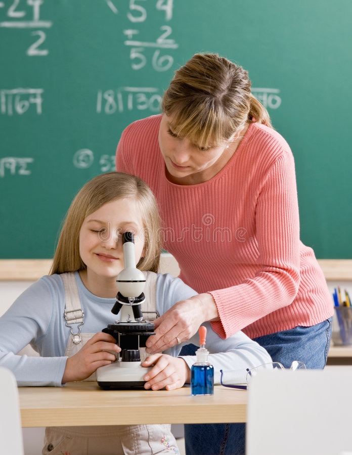Teacher helping student adjust microscope royalty free stock image