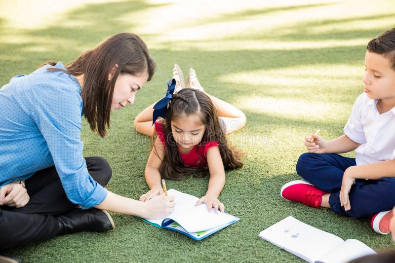 Teacher helping a student with her work. Patient female teacher helping her preschool student with a writing assigment while they take their class outdoors royalty free stock photo