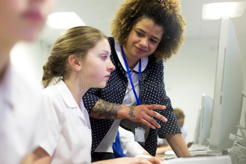 Teacher Helping Student in Lesson stock image