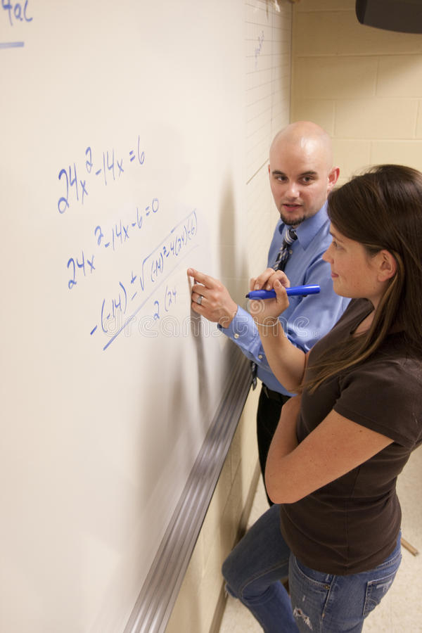 Teacher Helping Student With A Math Problem On A Whiteboard. Stock ...