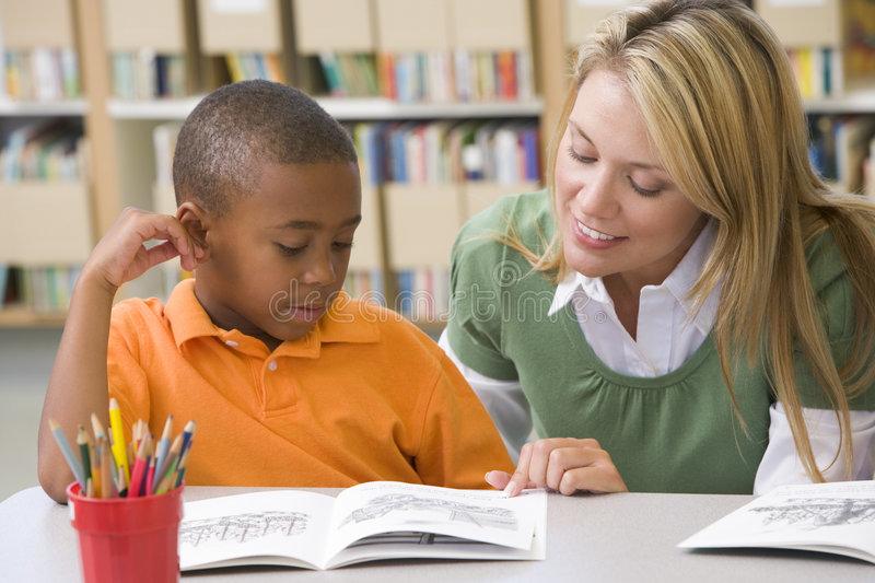 Teacher helping student with reading skills stock photo