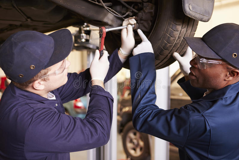 Teacher Helping Student Training To Be Car Mechanics royalty free stock photography
