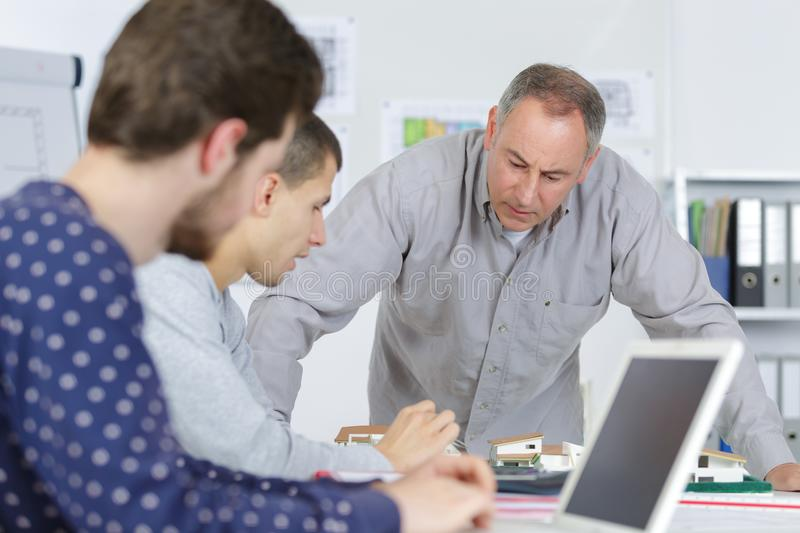 Teacher helping it student with work stock photos