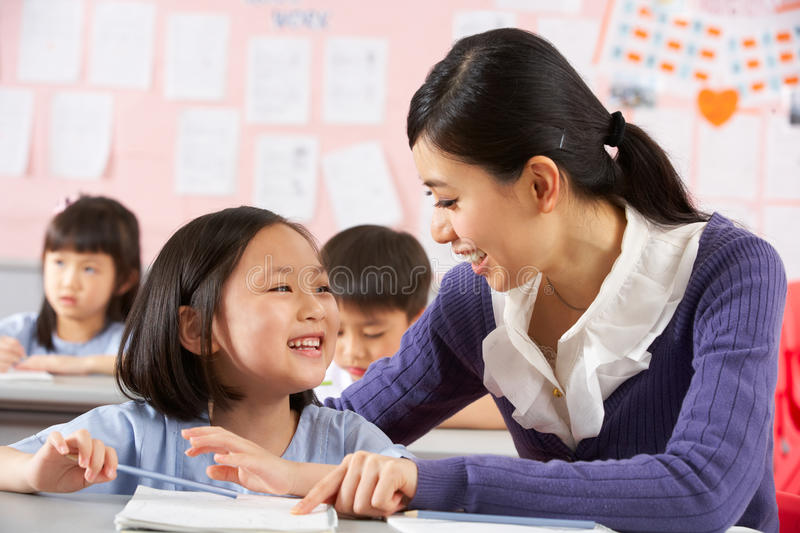 Teacher Helping Student Working In Chinese School stock photo