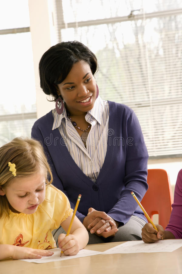 Download Teacher Helping Students stock image. Image of inside - 12529175