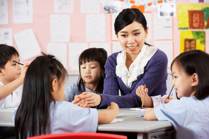 Teacher Helping Students During Art Class. In Chinese School Classroom stock photography