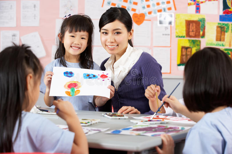 Teacher Helping Students During Art Class. In Chinese School Classroom stock photos