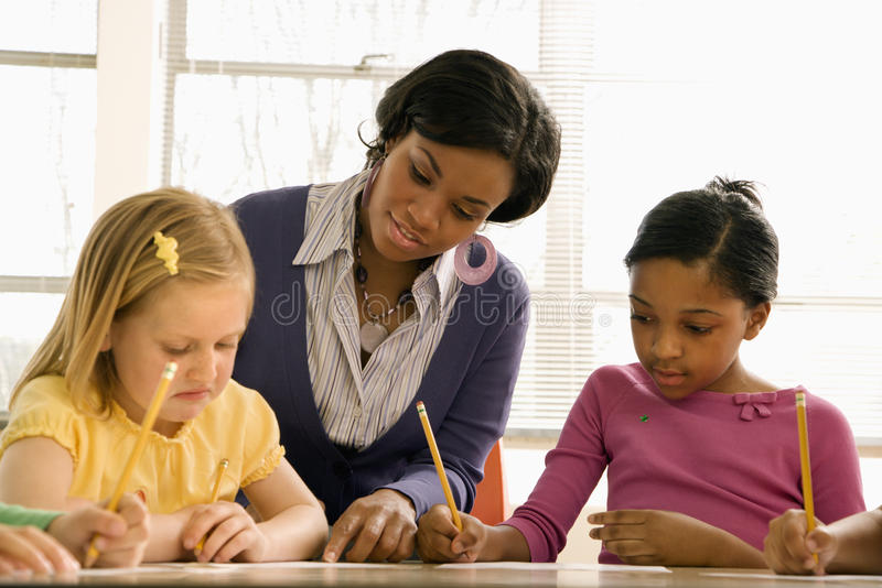 Download Teacher Helping Students With Schoolwork Stock Image - Image: 12529157