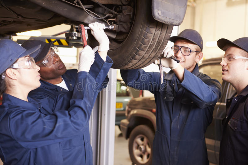 Teacher Helping Students Training To Be Car Mechanics stock photos