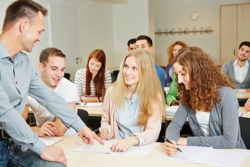 Teacher helping students in university class stock image