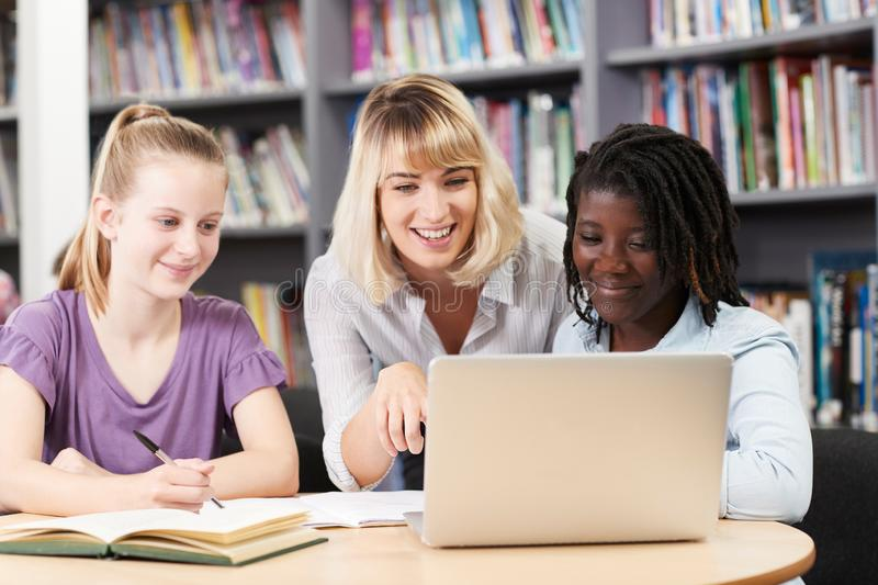 Teacher Helping Two Female High School Students Working At Laptop In Library royalty free stock photo