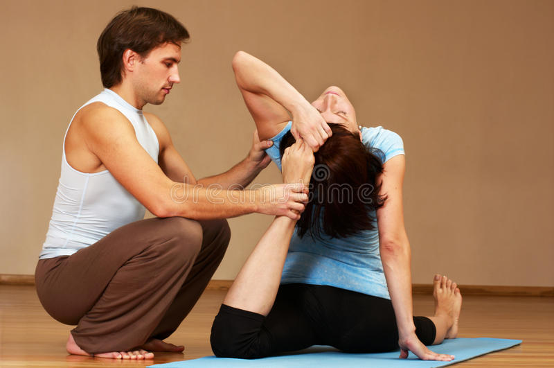 Teacher helping with yoga pose royalty free stock photo