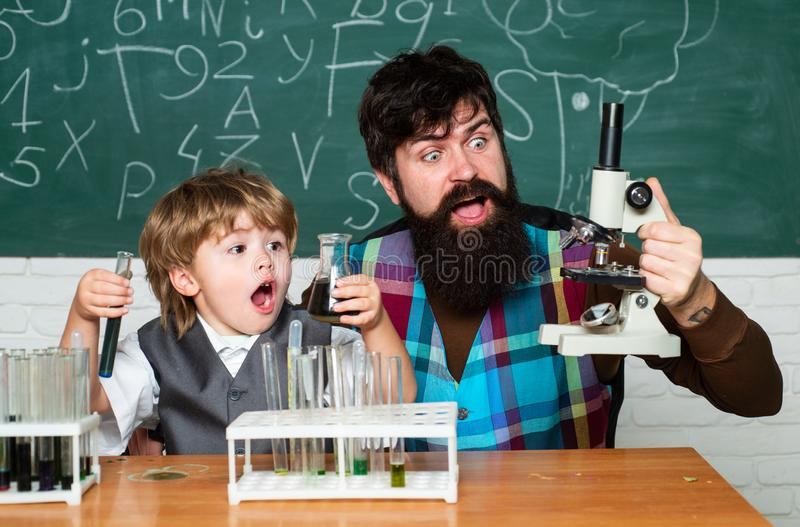 Teacher helping young boy with lesson. Homeschooling. Teacher helping pupils studying at desks in classroom. Ready for. School. Daddy and son together royalty free stock image