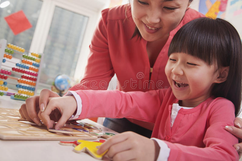 Teacher Helping Young Girl with Cut-Out Alphabet Letters stock photo