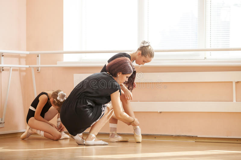 Teacher helping young students to prepare for pointe-work stock images