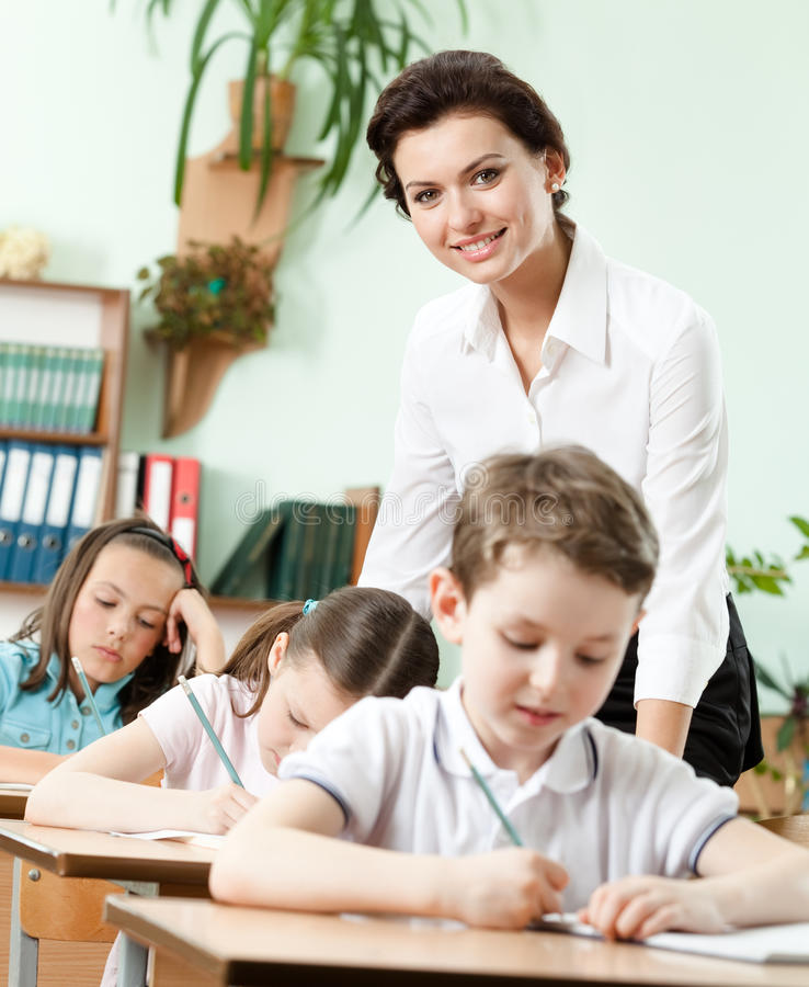 Download Teacher Helps Her Pupils To Do The Task Stock Image - Image: 26219151