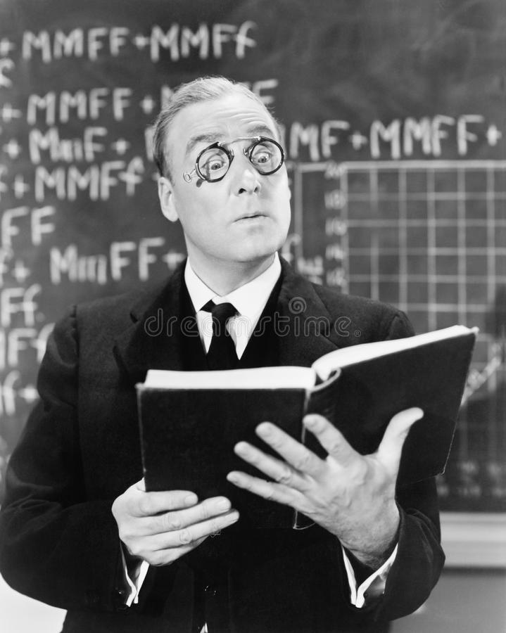 Teacher holding a book in front of a black board looking surprised stock images