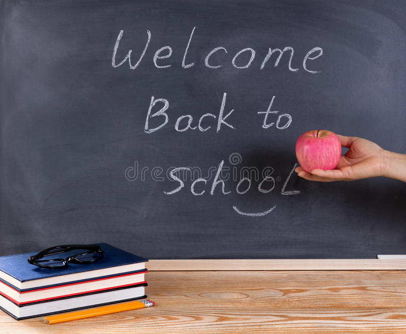 Teacher holding red apple in front of chalkboard with welcome ba stock photography