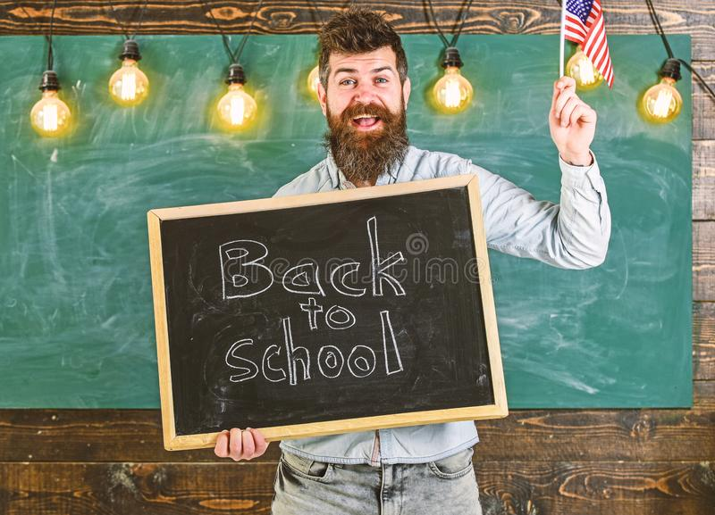 Teacher holds blackboard with written phrase back to school and flag of USA. Man with beard on smiling face welcomes to. American school, chalkboard on royalty free stock photography