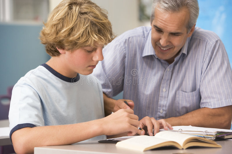 A teacher instructs a schoolboy royalty free stock images