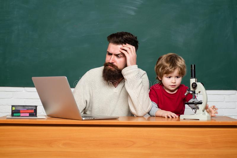 Teacher and kid. father teaching her son in classroom at school. Teacher helping young boy with lesson. Teacher helping stock images