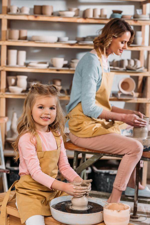 teacher and kid making ceramic pots on pottery wheels royalty free stock photo