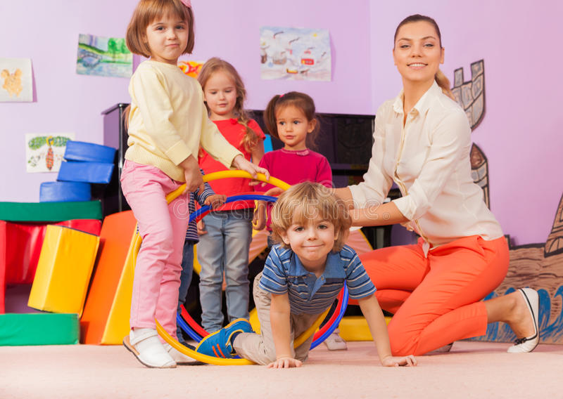 Teacher, kids in kindergarten play game with hoop. Group of kids and teacher in kindergarten set to play active game with hoops royalty free stock photos