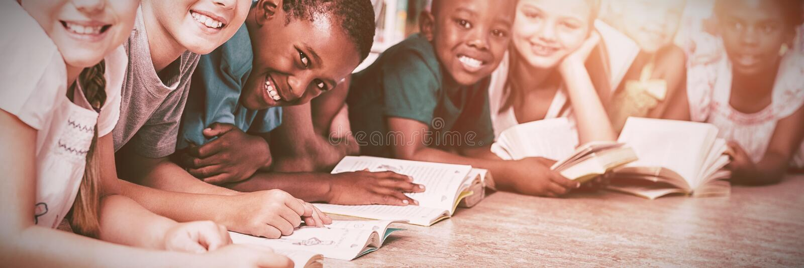 Teacher and kids lying on floor reading book in library stock photography