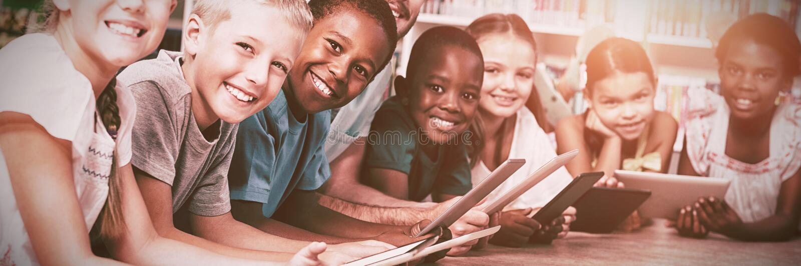 Teacher and kids lying on floor using digital tablet in library royalty free stock photo
