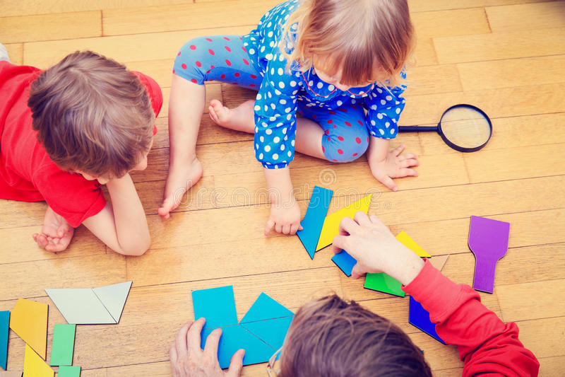 Teacher and kids playing with geometric shapes, early learning royalty free stock photos