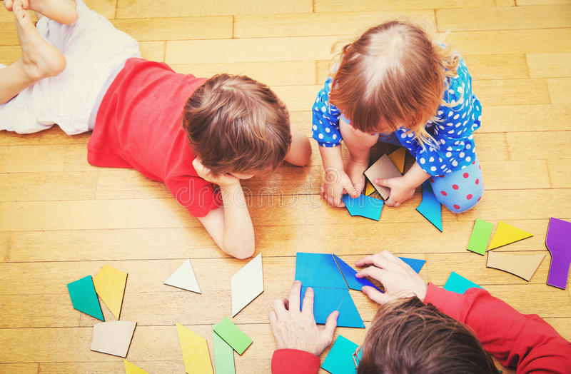 Teacher and kids playing with geometric shapes royalty free stock photography