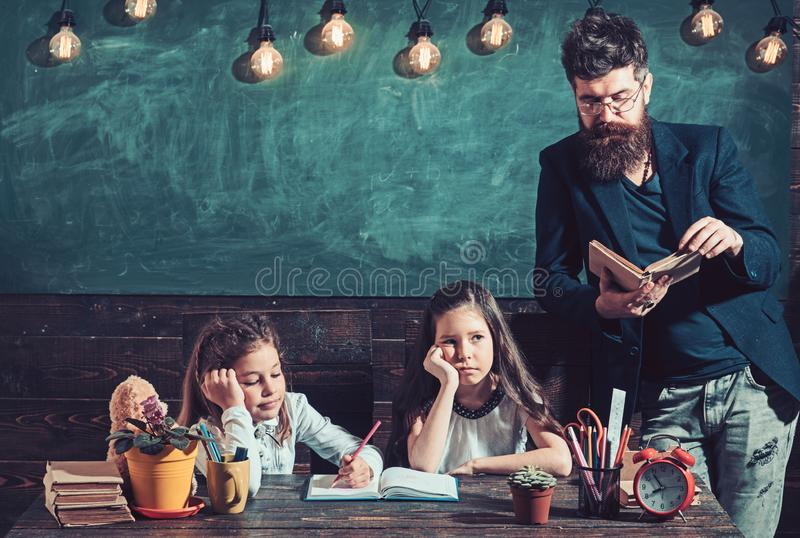 Teacher and kids reading book in library at elementary school stock photos