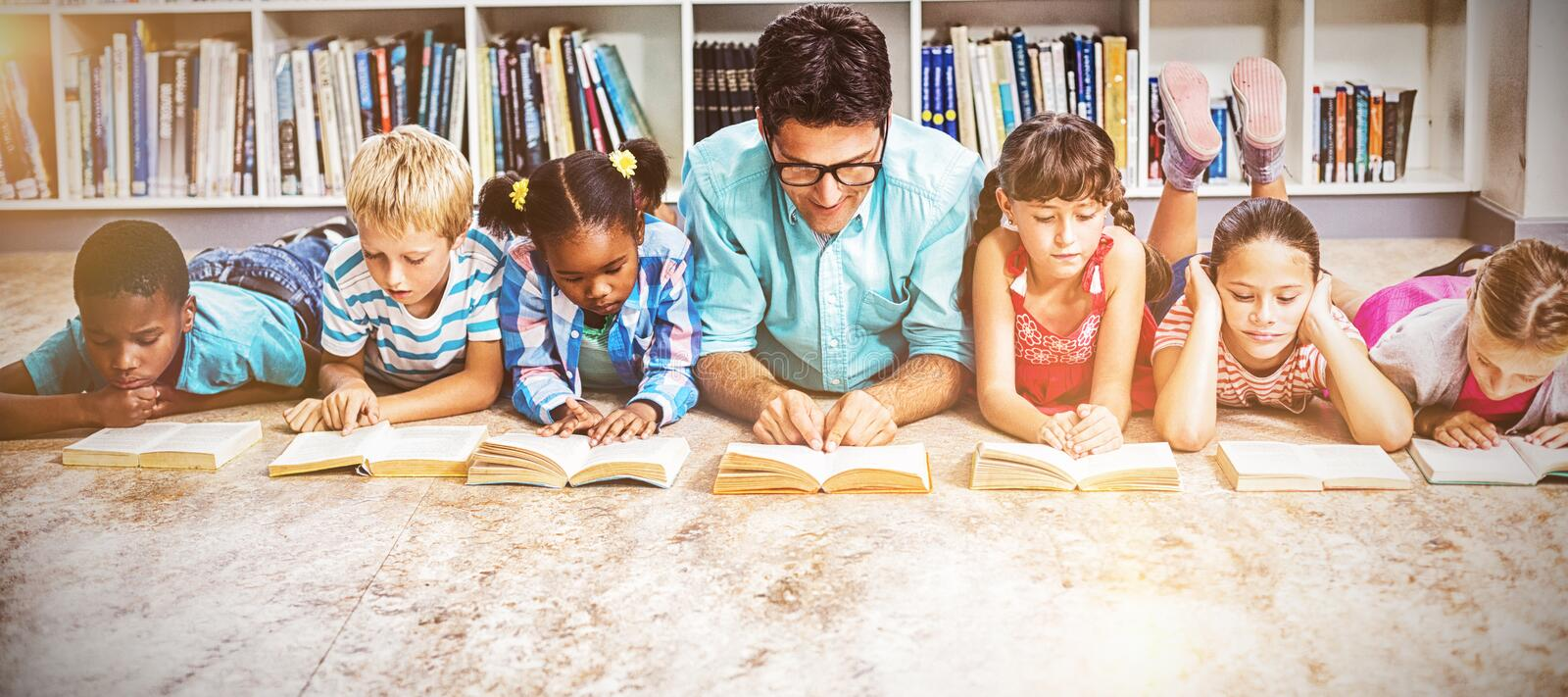 Teacher and kids reading book in library royalty free stock images