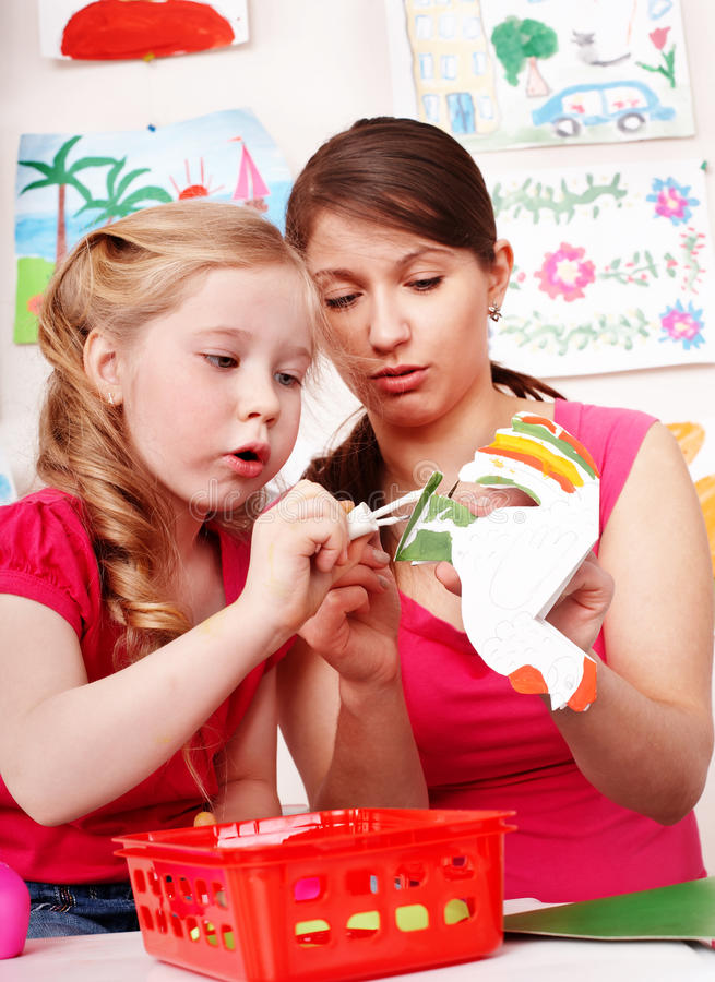 Teacher learn child in play room.