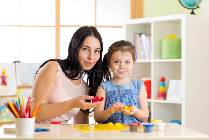 Teacher and little girl kid learn mold from plasticine in kindergarten royalty free stock photos