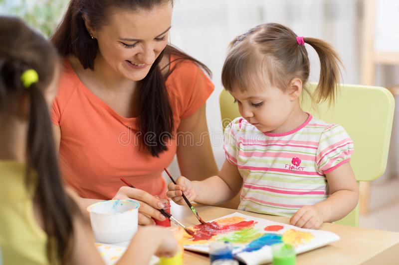 Teacher and little girls are painting in daycare center. Woman and children have a fun pastime. royalty free stock photos