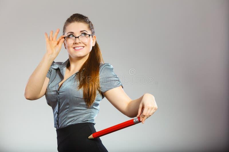 Teacher looking elegant woman holding big pencil royalty free stock photography
